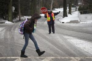A guard helps a student cross an intersection in Pelham,