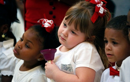 Angel Nevins, center, and her friend and classmate Jade Smith, left, wait for their signal to ring their hand bells as children from the Anderson Grove Head Start program in Caledonia, Mississippi, ring their hand bells to accompany several patriotic songs, Tuesday, February 26, 2013, at the Capitol in Jackson, Mississippi.