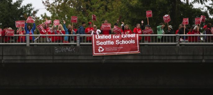 A group holds signs along a Northgate I-5 overpass in Seattle, as school district administrators and members of the Seattle Education Association (SEA) meet Thurs., Aug., 20 2015, for final contract negotiations, prior to the SEA's general membership meeting set for Monday.